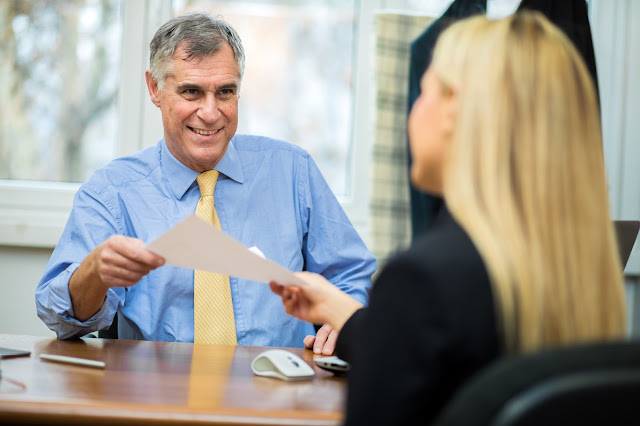 Image of a smiling bank manager with customer