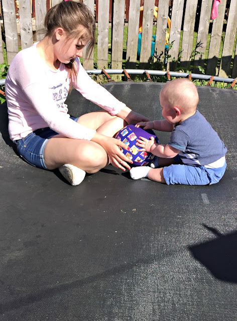 my baby and older child playing with bubabloon