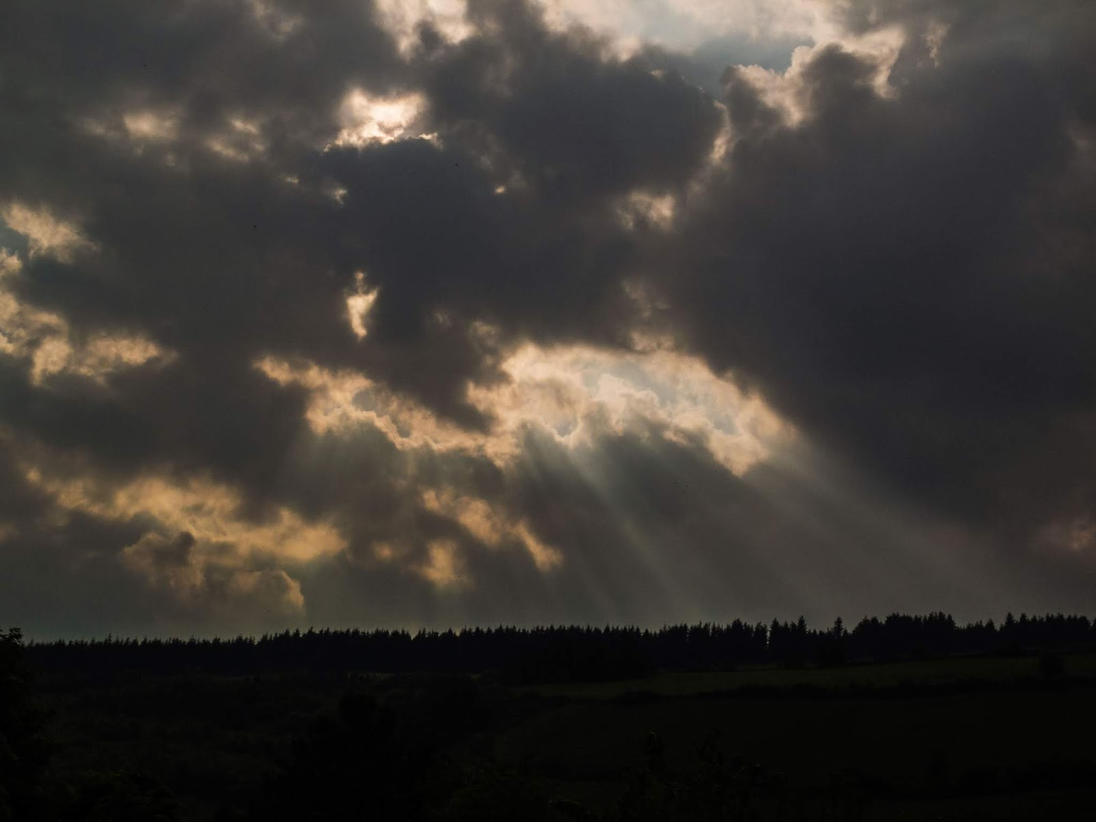 Sun rays coming out of dark clouds at sunset over a mountain top in Co.Cork.