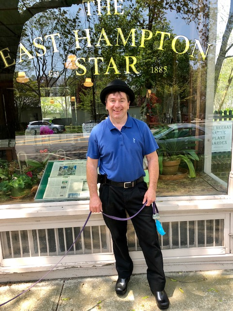 Smiling man wearing a bowler hat in front of the plate glass window of the East Hampton Star newspaper