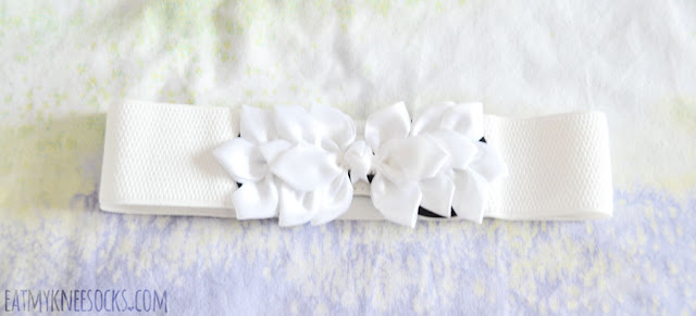 Details on the white ribboned floral waist cinching fashion belt accessory from Gamiss.