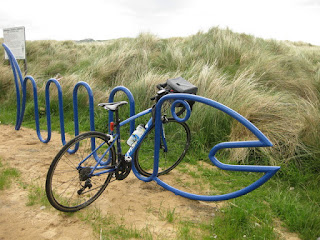 My blue Merida Ride 400 parked in a blue bike rack shaped like a fish, Ballymastocker Beach, County Donegal, Ireland
