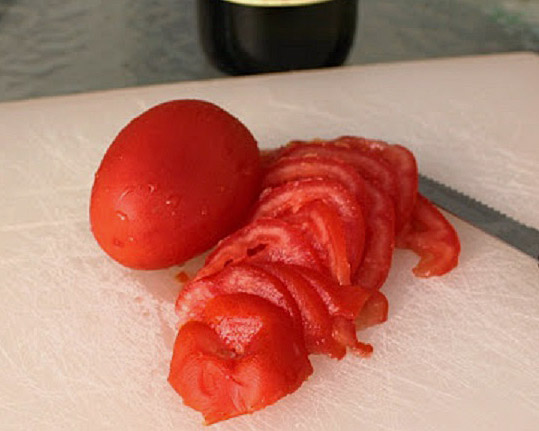 Plum tomato slices on a cutting board with a sharp knife