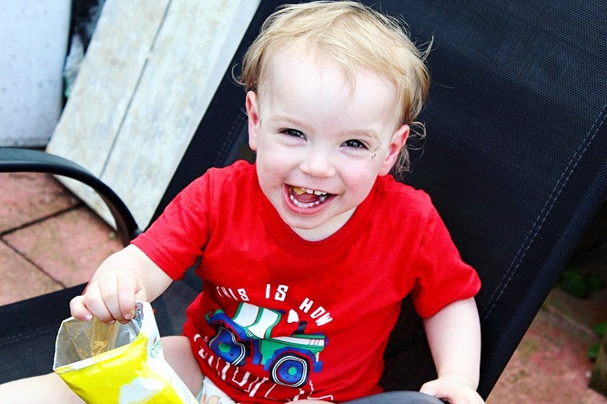 A small 1 year old boy is sitting on an adult sized chair, with a big open grin on his face, holding a bag of crisps. He wears a red top with a tractor on.