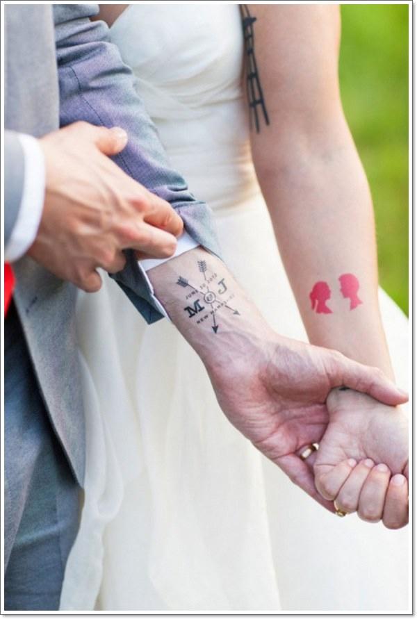 una pareja en el dia de su boda, enseñan sus tatuajes de pareja