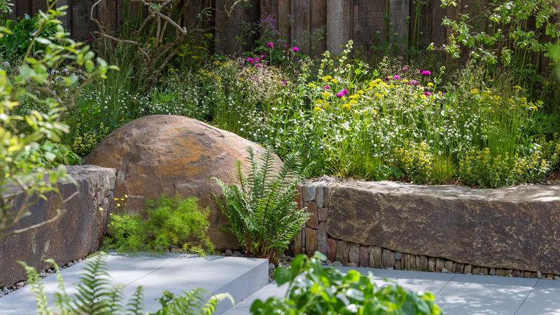 jardin con muro de piedra seca y plantas