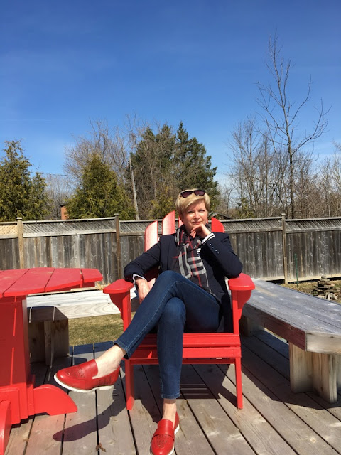woman in jeans, navy jacket, plaid scarf, and red shoes sitting in a red deck chair