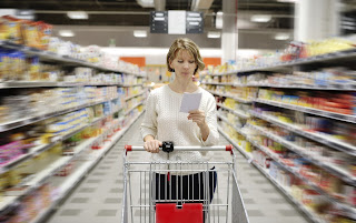 Woman in grocery store pushing a cart looking at a list.