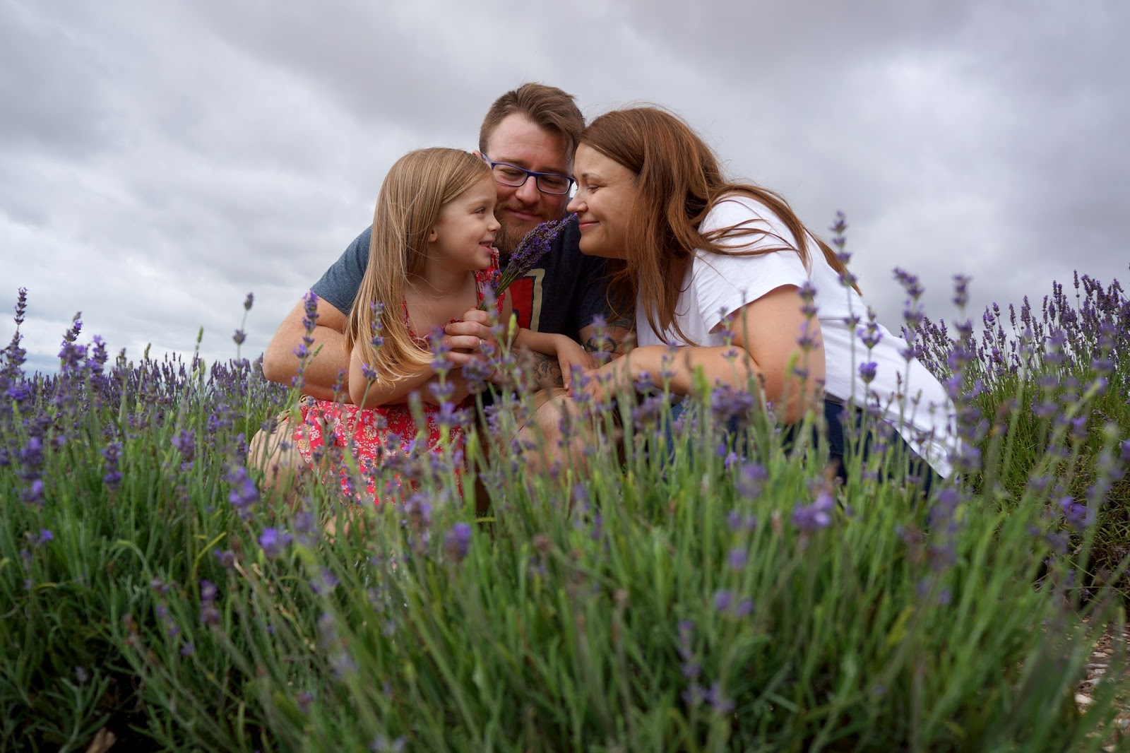 family at a lavender field smelling flowers