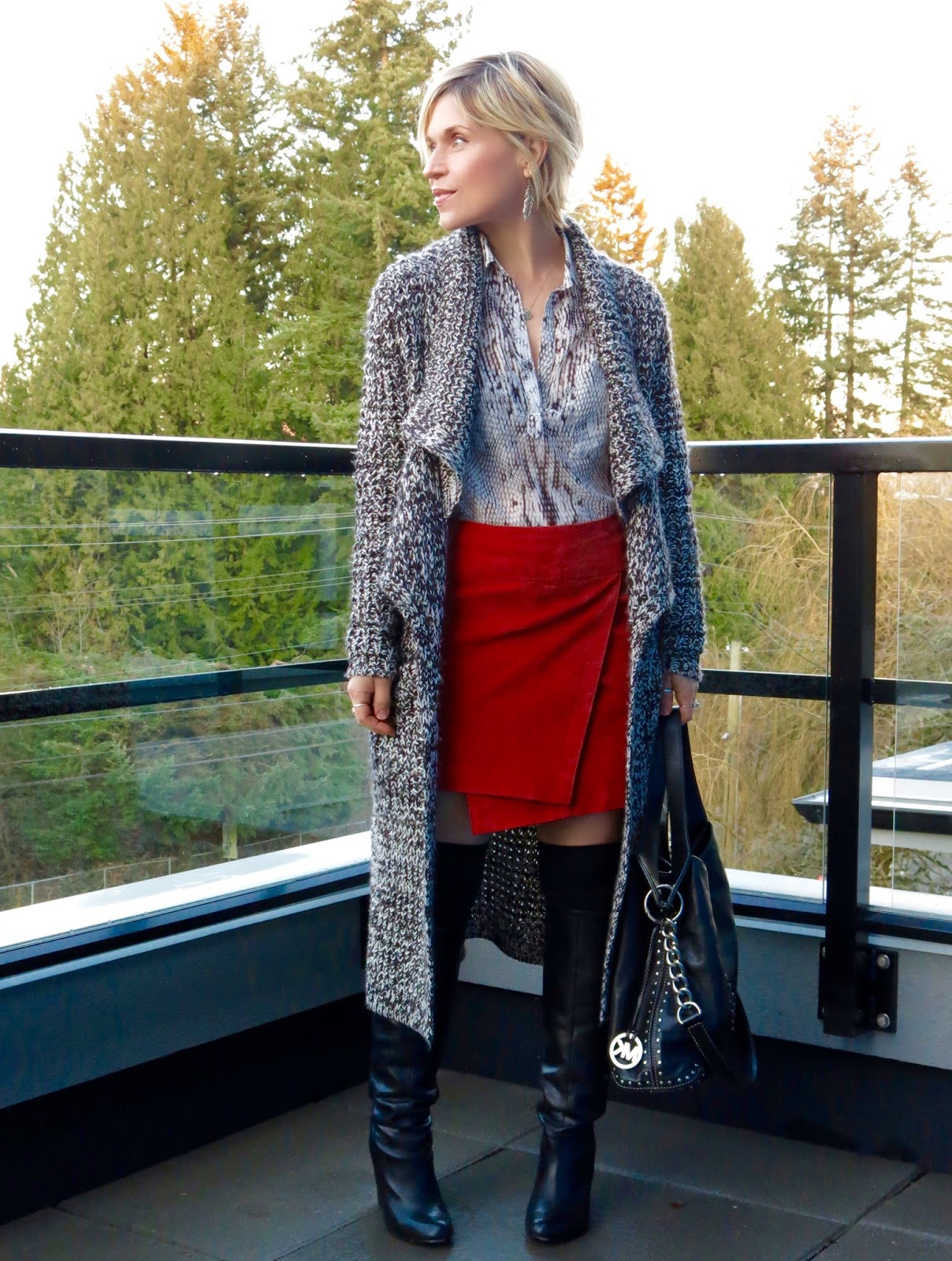 styling a red suede envelope skirt with a snake-print blouse, over-the-knee socks, tall boots, and a sweater coat