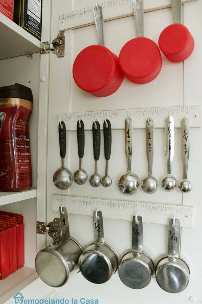 inside the cabinet door is used to store measuring cups and spoons