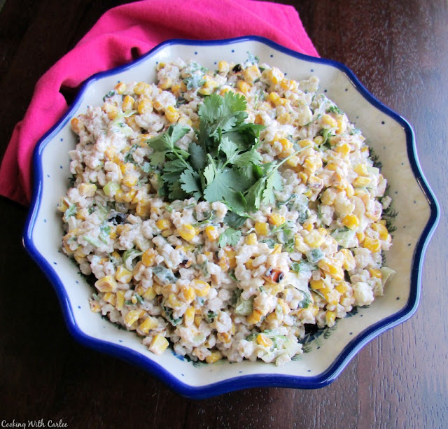 serving bowl filled with corn and barley salad topped with cilantro