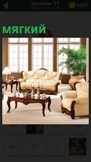 В комнате стоят мягкие диван и кресла напротив больших светлых окон