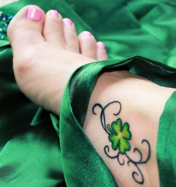 pie femenino, entre sedas, lleva tatuaje de trebol en el empeine