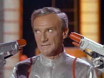 Dr. Smith with two guns at his head in Lost In Space 1965 movieloversreviews.blogspot.com