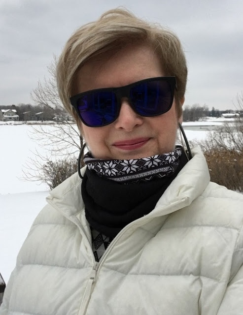 smiling woman in white down jacket, black and white neck warmer, blue tinted sunglasses standing in front of snow covered river