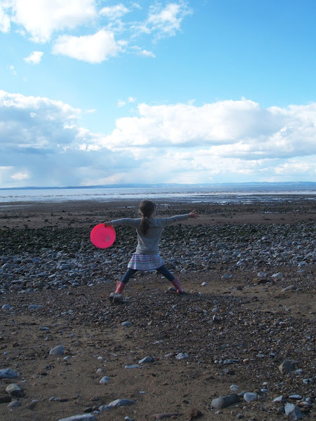 neon pink frisbee against bright blue sky and welsh coastline