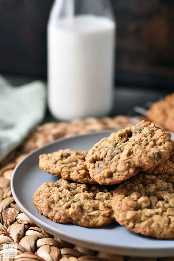 A plate of Quaker Oatmeal Cookies fresh out of the oven on a serving plate ready to enjoy with a tall glass of milk