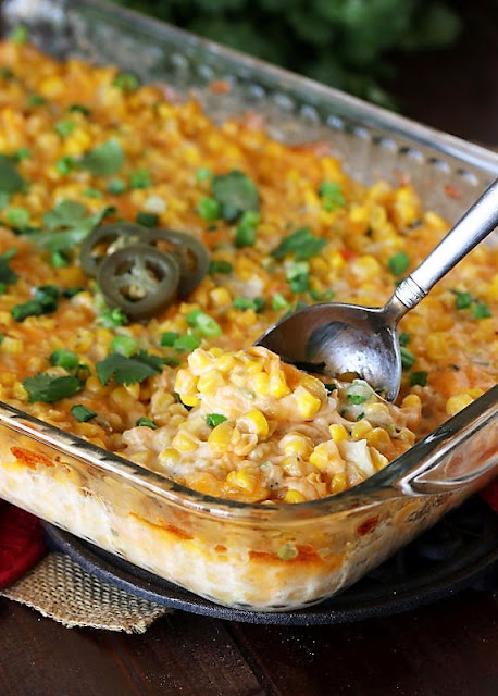 Cheesy Fiesta Corn Casserole in Baking Dish with Serving Spoon Image