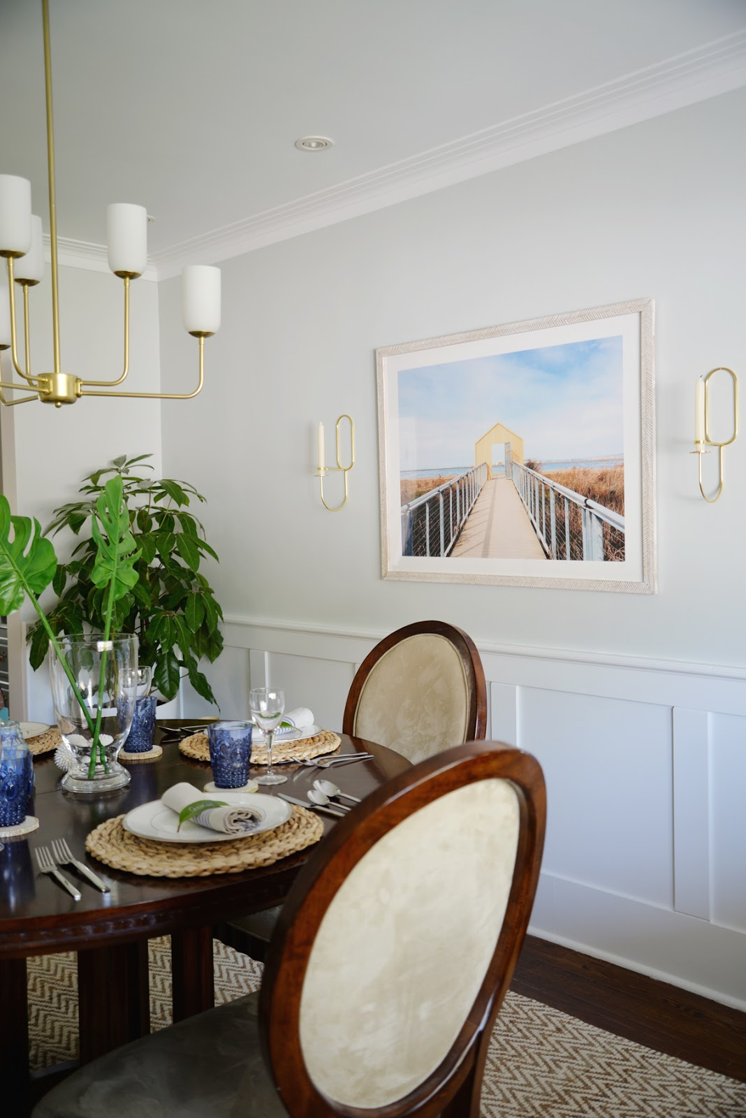 Rambling Renovators | tropical dining room, Lup Oblong Wall sconce, round dining table, Hinkley Harlow chandelier