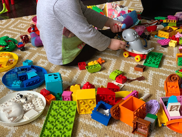 A toddler surrounded by DUPLO LEGO