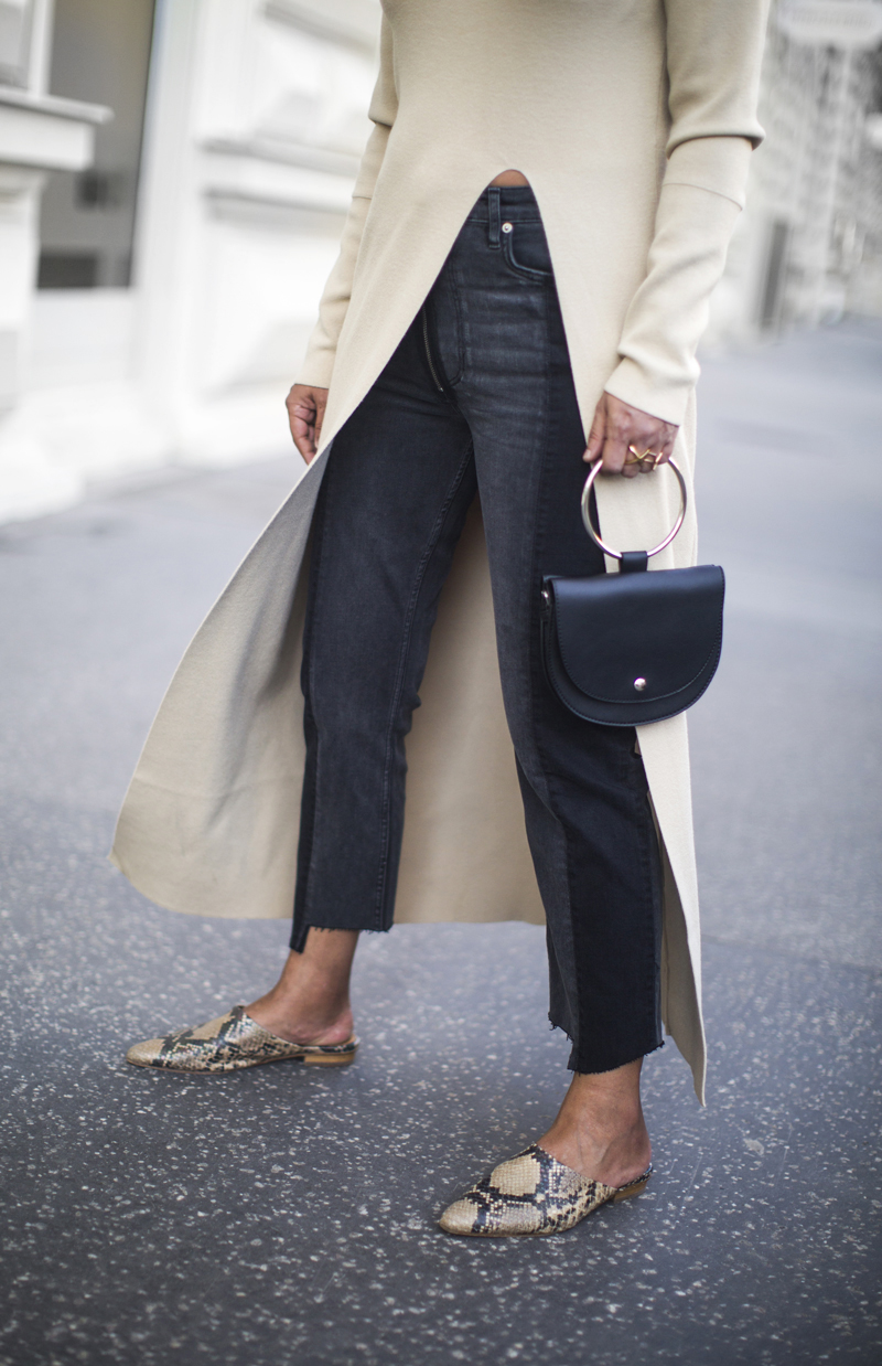 Spring Outfit Inspiration — Beige Long Split-Front Sweater or Long Cardigan, Black Raw-Hem -Jeans, Ring-Handle Mini Bag, and Snake-Print Mule Flats