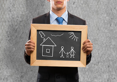 man holding up chalk board of family and house.
