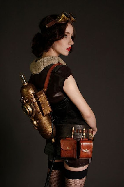 Female Steampunk Aviator costume. Her clothing includes goggles, shorts, fishnet stockings, sleeveless bomber jacket, utility belt and jetpack.
