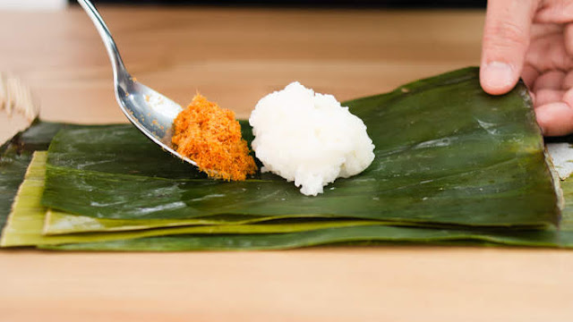 Add 1 tablespoon of fish floss to sticky rice on banana leaves photo
