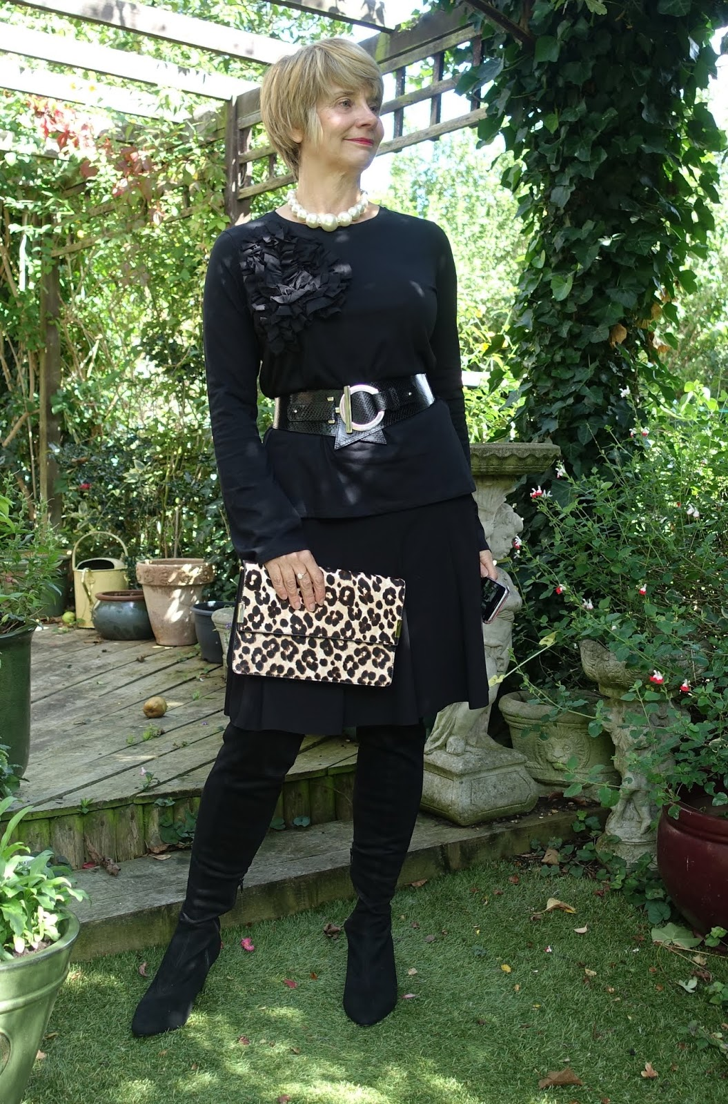 Image showing an over 45 woman showing how to add great accessories to a plain black outfit
