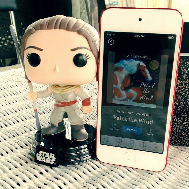 A large-headed Funko Pop bobblehead of Rey from Star Wars stands outdoors beside a white iPod with Paint the Wind's cover on it. The cover features a galloping white and chestnut paint horse.