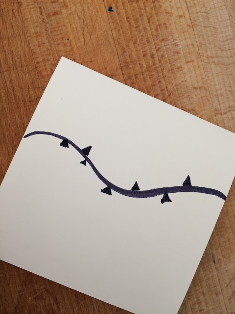 Folded cream card with a black curved line drawn on it