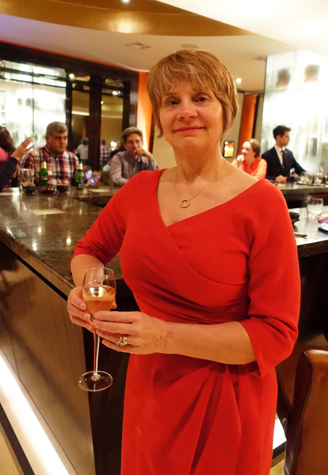 Image showing a woman in her 50s in a red dress standing by the bar of a luxurious London hotel
