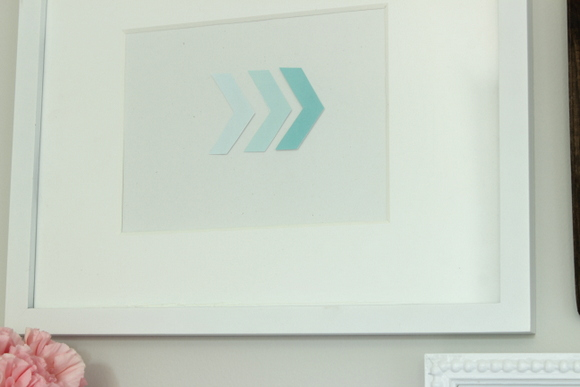 Framed blue arrow artwork on an office gallery wall
