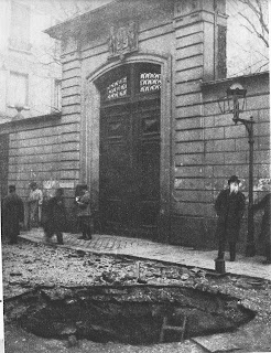 Black and white photo of a cement brick building which has a big door with walls on its sides, which are lower than the door. Above the door is a some type of seal sculpted with cement. In front of the door is a big hole almost twice the size of the width of the door, around which cements, asphalts and metal debris are lying around. A ladder is inside the hole. Five male pedestrians, all wearing fedoras, are passing by the hole but no one is directly staring at it.