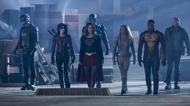 Screenshot of seven superheroes walking through an abandoned warehouse. From left to right, we see Spartan, Speedy, Supergirl, Atom, White Canary, Firestorm, and Heat Wave.