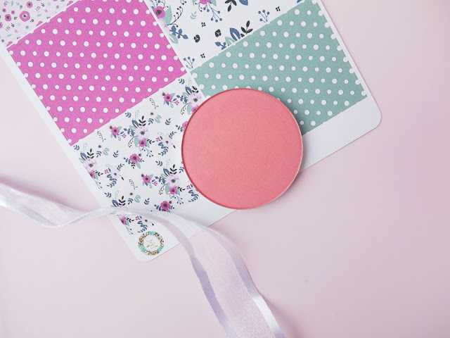makeup geek xoxo blush, a coral pink shade, sat on a pink background with a white ribbon beside it