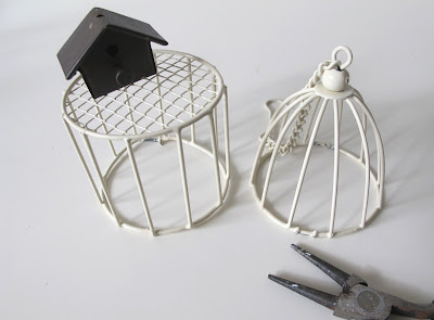 Modern dolls house miniature wire side table, with metal bird cage on top, next to a modern dolls house miniature wire cage-shaped light shade, and a pair of pliers.