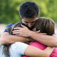 Kız ve erkek çocuklarına sarılarak şefkat gösteren bir baba
