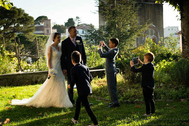Children taking pictures of the bride and groom