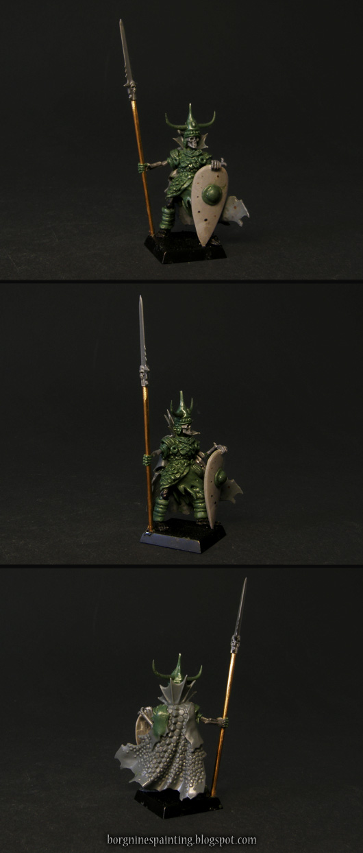 An unpainted, kitbashed Wight King miniature, carrying a spear made out of a brass rod, kite shield and wearing a flowing dragonskin cape.