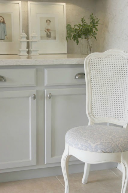 Pretty kitchen with blue-grey cabinets, quartz counter, and vintage chair - Hello Lovely Studio