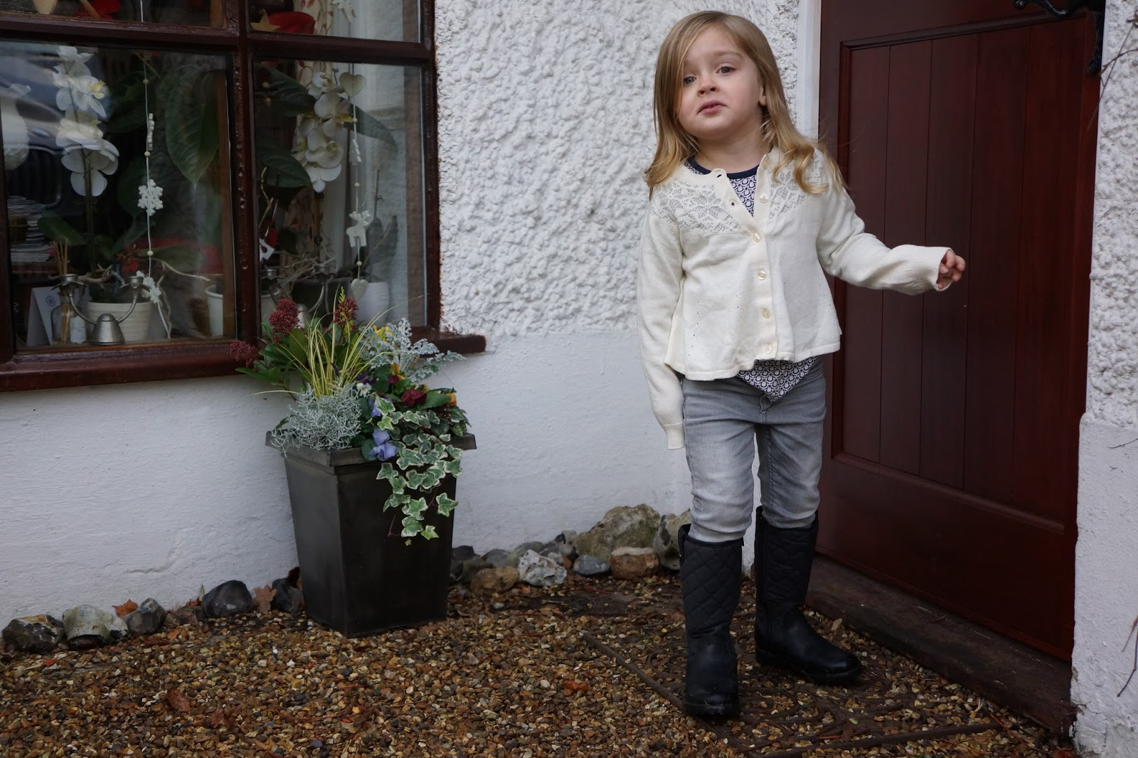 young girl in grey jeans black boots and white christmas cardigan