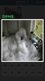 около окна стоит ванна с пеной и внутри сидит человек