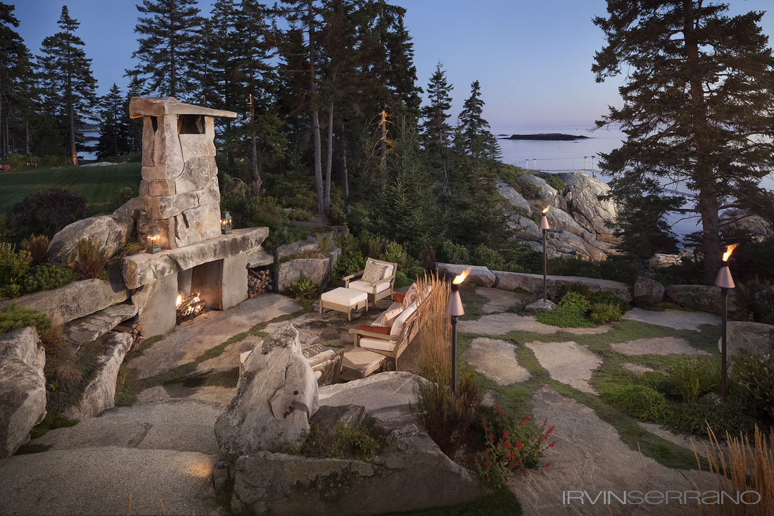 A lit, rustic fireplace made of stone sits on a stone patio overlooking the ocean at a Southport estate in coastal Maine.