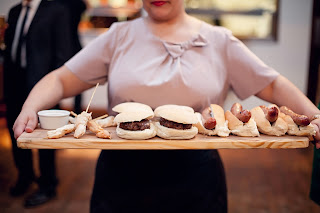 Woman holds a wooden tray with a selection of burgers and dips for the reception