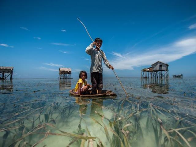 Foto de Ng Choo Kia - Crianças usam uma canoa tipica para pescar