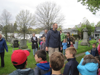 Man talking to a group of students in cemetery