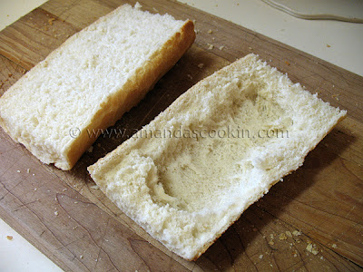 A photo of a French loaf sandwich sliced in half with bread pulled out of the bottom half to make a bowl.