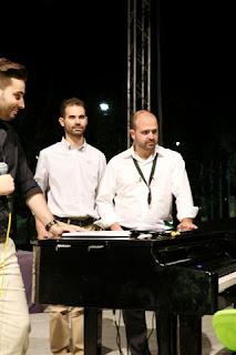 Ο Β. Αυγουλάς και ο Γ. Γαβράς παρακολουθούνε το Μίμη Πλέσσα ενώ παίζει πιάνο